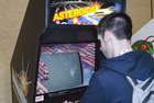 Man plays classic arcade cabinet Asteroids