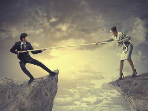 Business man woman pull rope tug of war cliff clouds struggle battle