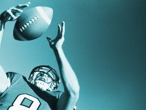 toned low angle view of a football player catching the ball stk17248spo