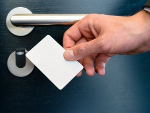mans hand with key card to hotel room door