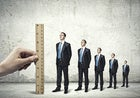 row of business man decreasing in size standing against ruler