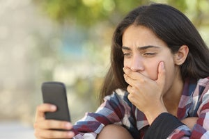 teenager looking at cell phone sextortion stock image