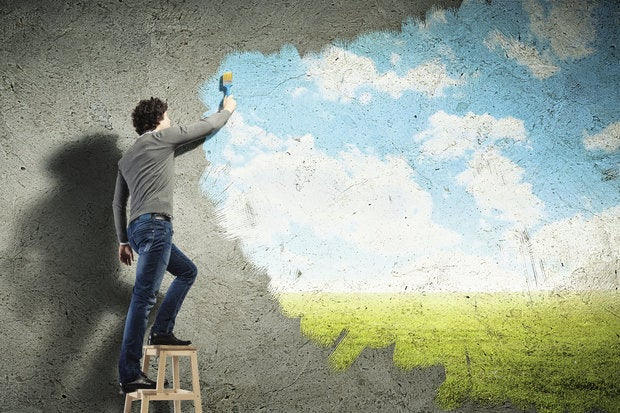 young millennial painting clouds on concrete wall