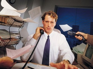 Efficiency - a busy man at his desk, surrounded by chaotic paperwork