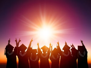 graduates in silhouette with sun setting behind them