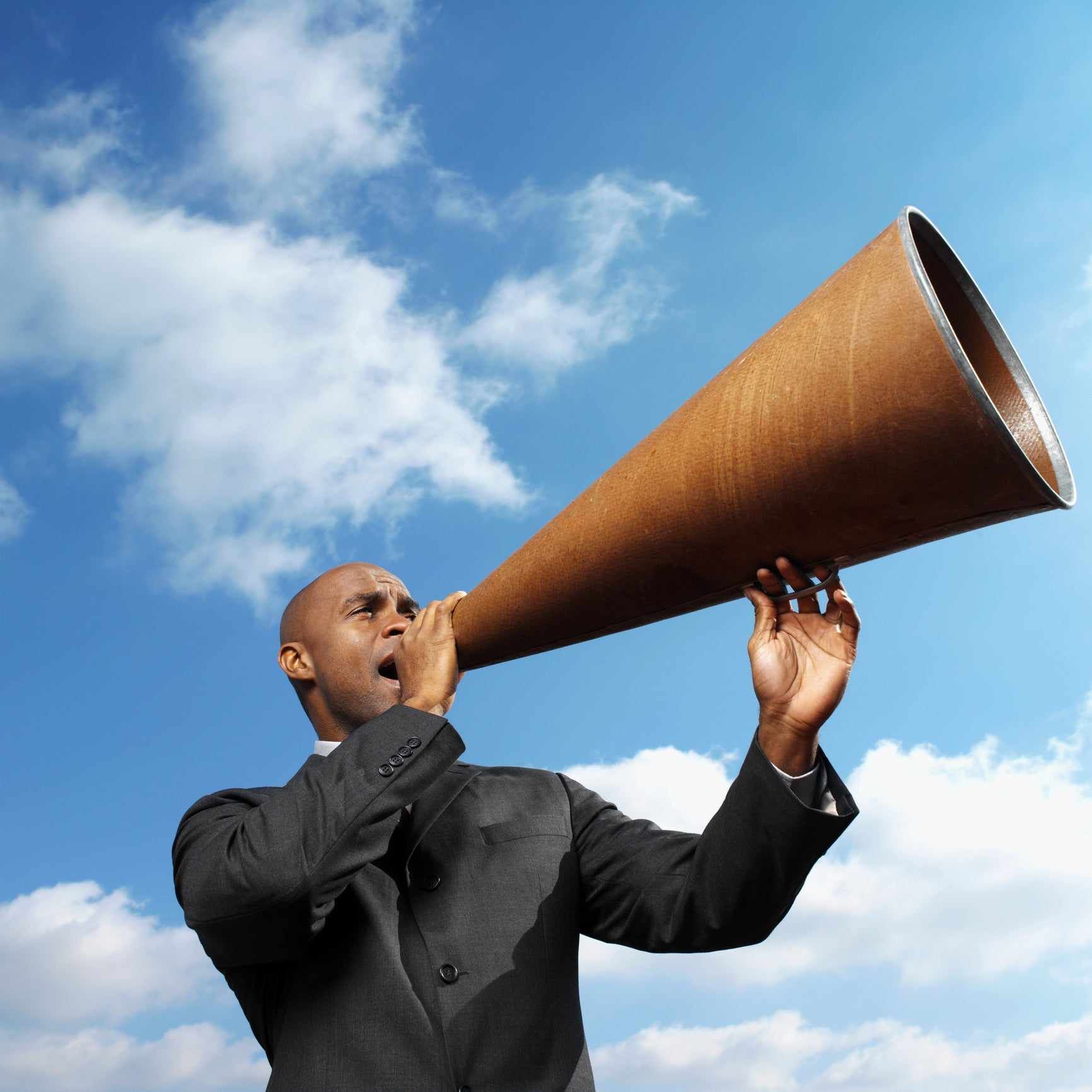 man holding large megaphone against blue cloudy sky
