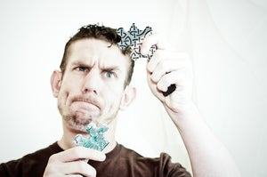 man solving jigsaw puzzle pieces